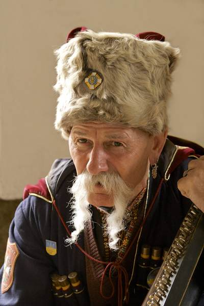 Old Polish male musician wearing military outfit with gun cartridges attached with fur hat and badges playing a traditional Polish stringed instrument in the Cloth Hall in Rynek Glowny Krakow Crakow in Poland Europe