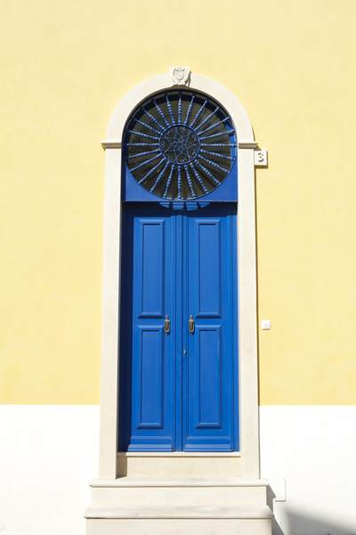 Blue wooden door and yellow painted house in the small Portuguese town of Sao Martinho do Porto, Alcobaca, Leiria District, on the Silver Coast of Central Portugal, Europe