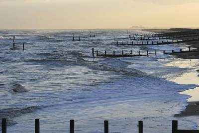 Waves roll in on Southwold beach at sunset on a winters day in Suffolk with Sizewell Bin the distance, United Kingdom, Europe