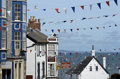 View down Pound Street in the summer with colourful bunting and flags in Lyme Regis in Dorset in South West England, United Kingdom Europe